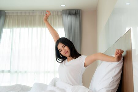 Asian Woman stretching hands and body in bed after wake up in bedroom at home. Concept for start new day with happiness. Copyspace on the left. Young happy working female life Imagens - 133870999