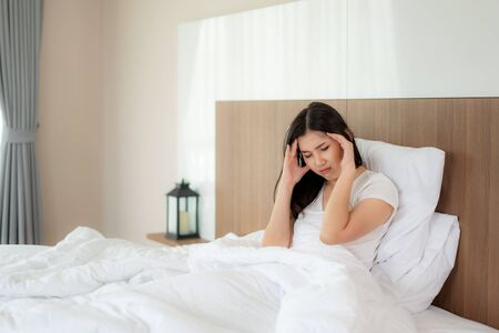 Attractive young Asian woman wake up on her bed holding their hand from headache and looking unhappy and feeling headache  migraine  stress  sick. Concept of womens health care.