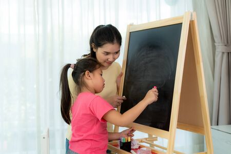 Asian mother playing with her daughter drawing together with color chalk in blackboard at table in living room at home. Parenthood or love and bonding expression concept.