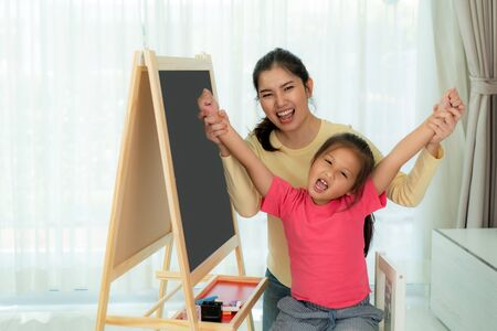 Happy successful Asian kindergarten student and her mother hands raised up to celebrate the successful to do drawing in blackboard in living room at home. Child art education or family love concept.
