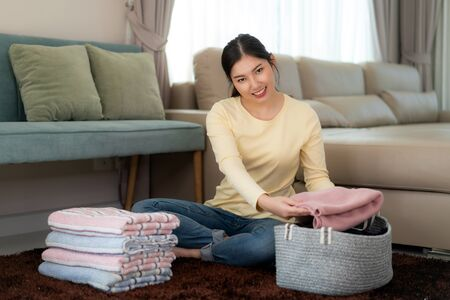 Smiling Asian woman holding clean folded clothes at home. Pretty young lady sitting in floor with sofa in background. Laundry and household concept. Front view.