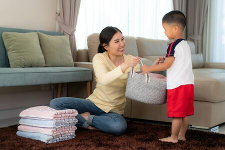 Beautiful Asian mother and child boy little helper are having fun and smiling while doing help her mother folded clothes laundry at home. Happy family. Imagens - 133871008