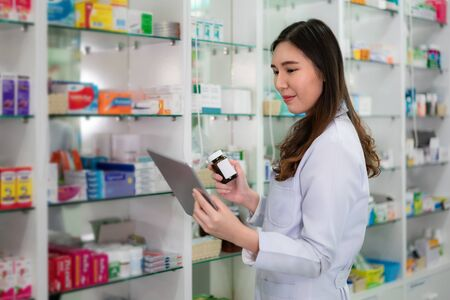 Confident Asian young female pharmacist with smile holding a medicine bottle and searching that product in digital tablet database in the pharmacy drugstore. Medicine, pharmaceutics, health care and people concept.