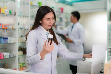 Confident Asian young female pharmacist with smile holding a medicine bottle and searching that product in the computer database in the pharmacy drugstore. Medicine, pharmaceutics, health care and people concept.