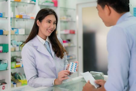 Confident Asian young female pharmacist with a lovely friendly smile and explaining capsule medicine to her customer in the pharmacy drugstore. Medicine, pharmaceutics, health care and people concept. Imagens