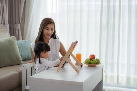 Happy Asian young mother and daughter playing with abacus, early education at home. Parenthood or love and bonding expression concept. Imagens