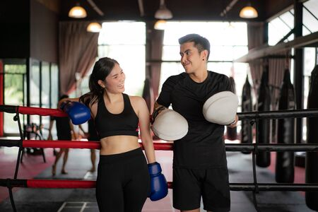 Asian boxer sports girl and trainer looking  smile while leaned on black red ropes on boxing ring, and have a rest after hard training in black loft gym. Sporty fit for healthy lifestyle Asian model of boxing gym concept. Imagens