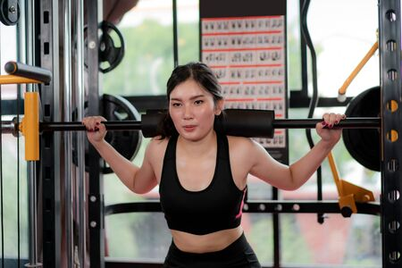 Asian young woman playing Gym Equipment to exercising build her boday alone in gym, Sporty fit for healthy lifestyle Asian model of boxing gym concept.