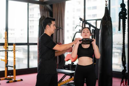 Asian beautiful sport Woman in gym with exercising power gymnastics with weight and personal fitness trainer practice to her. Sporty fit for healthy lifestyle Asian model of boxing gym concept. Imagens