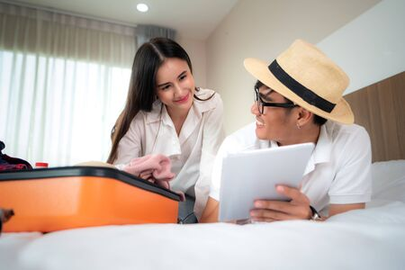Happy couple packing suitcase on bed in bedroom and lying and looking digital tablet for search and planning travel trip online. Asian backpacker travel lifestyle concept. Imagens