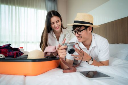Happy Asian couple unpacking suitcase on bed in bedroom when they arrive in hotel room and lying and looking photo in travel trip at camera. Asian backpacker travel lifestyle concept.
