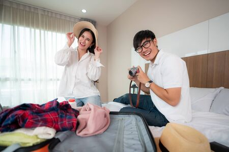 Happiness Asian couple traveler packing suitcases preparing for travel vacation together and looking fun when they preparing to journey. Asian backpacker travel lifestyle concept. Imagens