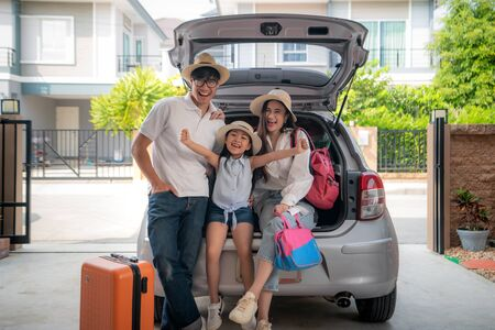 Portrait of Asian family with father, mother and daughter looks happy while preparing suitcase into a car for holiday. Shot in the house garage. Imagens - 134713786