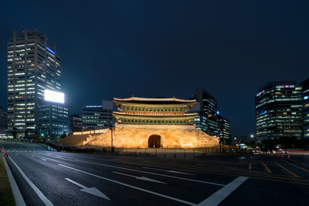 Namdaemun gate in Seoul business district area skyline view from street at night in Seoul ,South Korea. Asian tourism, modern city life, or business finance and economy concept