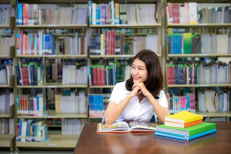 Asian students sitting in chair and looking and thinking about something while she reading and researching on the study in the library. Education teenager and wisdom concept.  Imagens