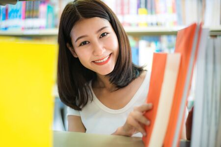 Cheerful female Asian student girl reading book during break between lesson near bookshelves in modern interior library of university. Education, wisdom and study concept.