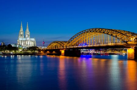 Hohenzollern bridge with t Cologne Cathedral and Rhine river during sunset in Cologne, Germany. Europe tourism, history building, or tradition culture and travel concept