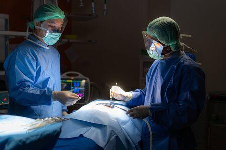 Dokterchirurgieteam in de operatiekamer van een keizersnede tijdens de bevalling in het noodhospitaal van de patiëntverpleegster. Stockfoto