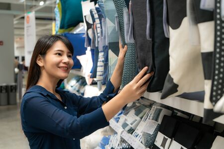 Asian woman are choosing to buy new pillows in the mall. Shopping for groceries and housewares are needed in markets, supermarkets or big shopping centers.