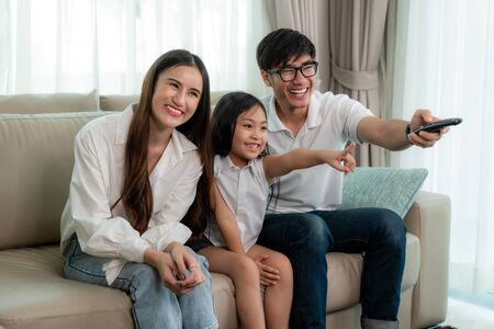 Candid of happy Asian family enjoy weekend activity by watching TV program at home. Father, mother and daughter sitting on sofa table holding remote on hand and pointing toward to TV