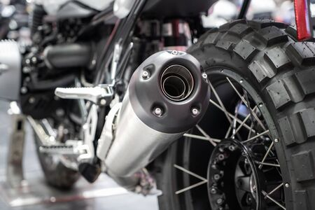 Close-up of exhaust or Intake of black sport racing Motorcycle with new tire and wheel in showroom. Low Angle Photograph Of Motorcycle. Stock Photo