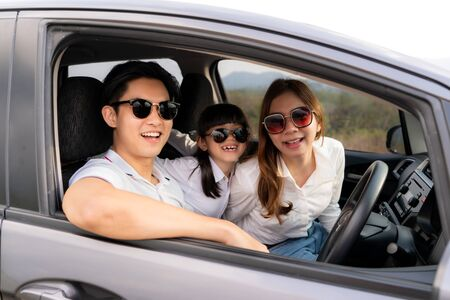 Happy Asian family with father, mother and daughter wear sunglass in compact car are smiling and driving for travel on vacation. Car insurance or rental and family happy to journey concept.