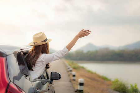 Woman at spree time relaxing and enjoying road trip. Young Asian happines female wearing hat inside compact black car with raise her hand out to the car window with mountain and lake view at sunny day in Thailand.