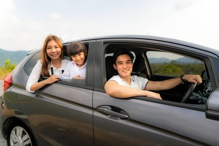 Happy Asian family with father, mother and daughter in compact car are smiling and driving for travel on vacation. Car insurance or rental and family happy to journey concept.