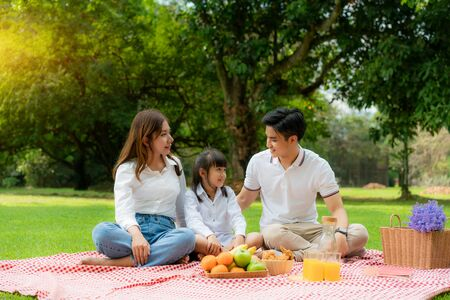 Asian teen family happy holiday picnic moment in the park with mother and daughter looking at father and smile to happy spend vacation time togerter in green garden with friut and food. Stock Photo