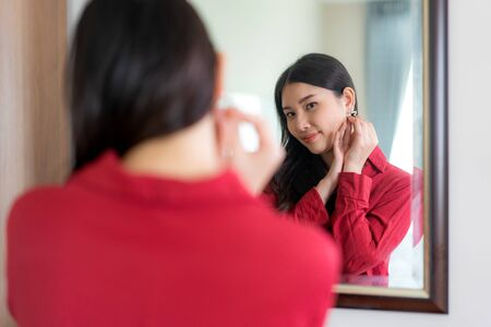 Beautiful Asian Woman wearing red dressed putting star earring looking in mirror in her bedroom at home. Makeup in morning getting ready before going to work.