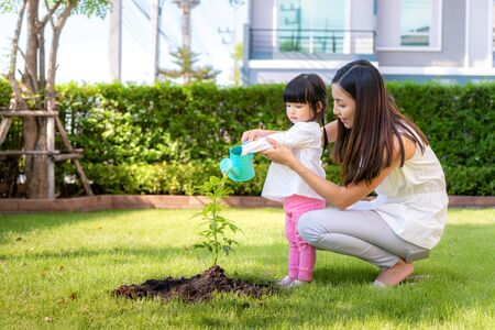 Asian family mother and kid daughter plant sapling tree and watering outdoors in nature spring for reduce global warming growth feature and take care nature earth. People kid girl in garden background.