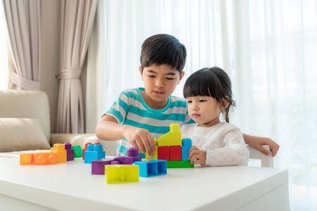 Un frère et une soeur asiatiques mignons jouent avec un concepteur de blocs de jouets sur la table dans le salon à la maison. Concept de lien entre frères et sœurs, amitié et apprentissage par le jeu pour le développement de l'enfant.