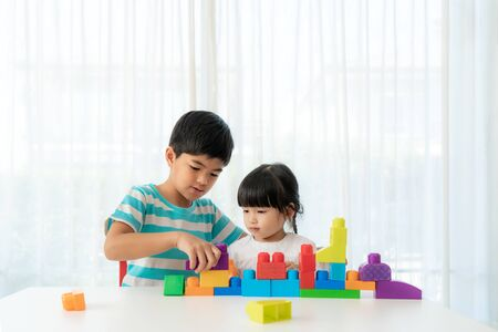 Asian cute brother and sister play with a toy block designer on the table in living room at home. Concept of bonding of sibling, friendship and learn through play activity for kid development. 版權商用圖片