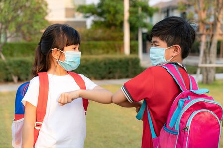 Elbow bump is new novel greeting to avoid the spread of coronavirus. Two Asian children preschool friends meet in school park with hands. Instead of greeting with a hug or handshake, they bump elbows instead.