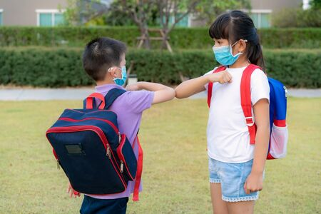 Elbow bump is new novel greeting to avoid the spread of coronavirus. Two Asian children preschool friends meet in school park with hands. Instead of greeting with a hug or handshake, they bump elbows instead. Stock Photo
