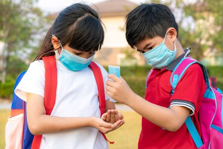 Asian boy student wear hygienic mask and press alcohol gel from bottle to hand's sister for protect  covid-19 coronavirus and epidemic virus after back from school. Banco de Imagens - 142519922