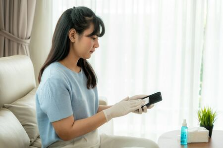 Asian woman is spraying alcohol, disinfectant spray on mobile phone, prevent infection of Covid-19 virus,contamination of germs or bacteria, wipe or cleaning phone to eliminate, outbreak of Coronavirus. Stock Photo