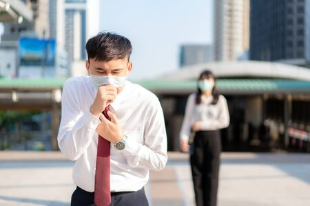 Asian ill businessman cough with mask with businesswoman in background to keep distance protect from COVID-19 viruses and people social distancing for infection risk and disease prevention measures.