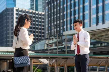 Pay respect is new novel greeting to avoid the spread of coronavirus. Two Asian young businessman and businesswoman friends meet in font of office building. Instead of greeting with a hug or handshake, they Pay respect instead. Foto de archivo