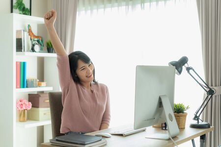 Beautiful Asian business woman work from home and celebrate with computer, success happy pose. E-commerce, university education, internet technology, or startup small business concept.