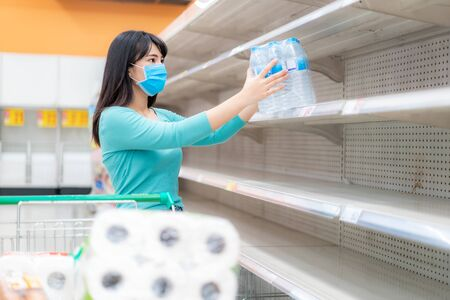 Asian woman pick up last water bottle pack at Supermarket empty shelves amid COVID-19 coronavirus fears, shoppers panic buying and stockpiling toilet paper preparing for a pandemic.