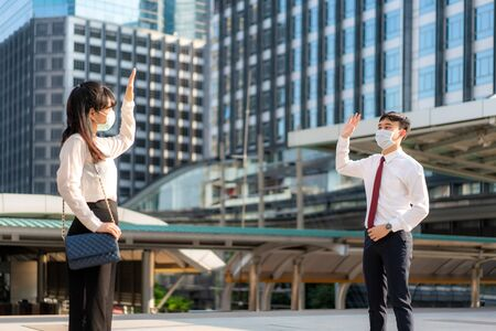 Asian business man and woman greet and say hello with business colleague and wearing mask standing distance of 1 meter distance protect from COVID-19 viruses for social distancing for infection risk and disease prevention measures.