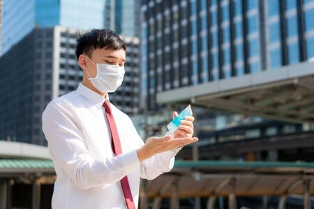 Asian business man using wash hand sanitizer gel dispenser, against Novel coronavirus (2019-nCoV) or COVID-19 in city downtown. Antiseptic, Hygiene and Healthcare concept.