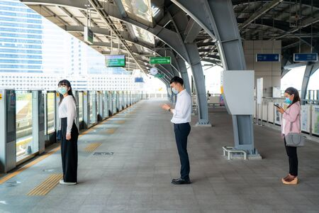 Three Asian people wearing mask standing distance of 1 meter from other people keep distance protect from COVID-19 viruses and people social distancing for infection risk and disease prevention measures. Foto de archivo