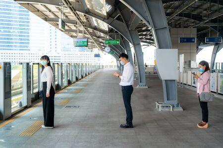 Drei asiatische Menschen, die eine Maske tragen, die einen Abstand von 1 Meter zu anderen Menschen tragen, halten Abstand zum Schutz vor COVID-19-Viren und Menschen, die sich für Maßnahmen zur Infektionsrisiko- und Krankheitsprävention sozial distanzieren. Standard-Bild