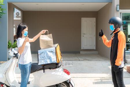 Asiatische frau holt liefertasche aus der box und daumenformular kontaktlos oder kontaktfrei vom lieferfahrer mit fahrrad im vorhaus für soziale distanzierung für infektionsrisiko. Standard-Bild