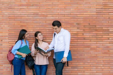 Three Asian students are discussing about exam preparation, presentation, study, study for test preparation in University. Education, Learning, Student, Campus, University, Lifestyle concept.