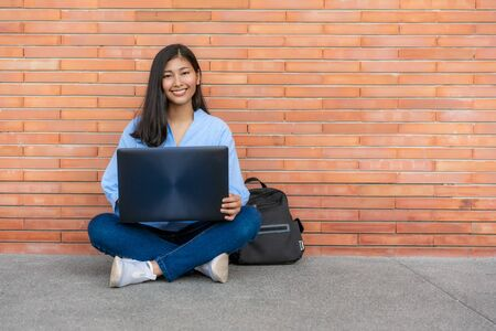Asian smiling woman student sitting and using laptop on brick background in campus. Happy teen girl high school student outdoors. Education, Learning, Student, Campus, University, Lifestyle concept. 版權商用圖片