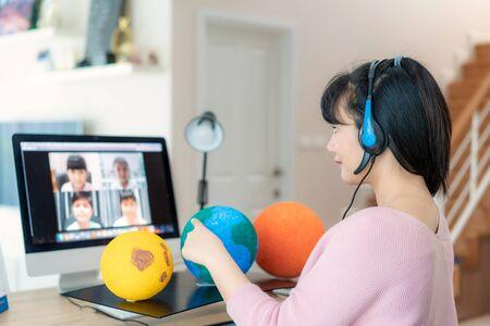 Enseignante asiatique enseignant le système solaire via l'apprentissage en ligne par vidéoconférence et élève joyeuse du primaire regardant le globe, l'enseignement à domicile et l'apprentissage à distance, en ligne, l'éducation et Internet. Banque d'images