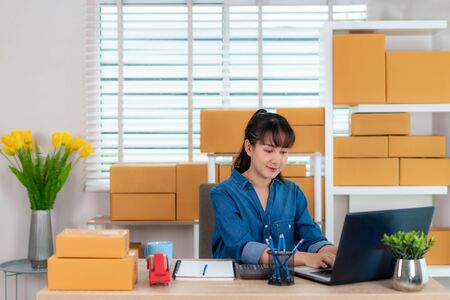 Asian owner business woman work at home for online shopping, chat with customer her notebook with laptop with office equipment, entrepreneur lifestyle concept
